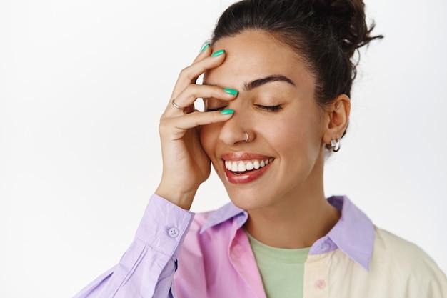 Glück und schönheit. nahaufnahme des attraktiven brünetten mädchens, lachend und lächelnd weiße zähne, augen schließen und gesicht sorglos berühren, auf weiß stehend