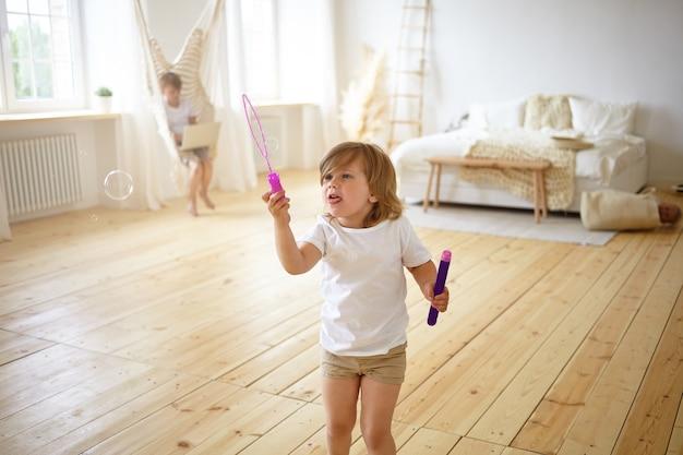 Glück und sorgloses kindheitskonzept. innenporträt des entzückenden glücklichen weiblichen kindes im t-shirt und in den kurzen hosen, die in der mitte des modernen wohnzimmers stehen, spaß haben, seifenblasen blasen,