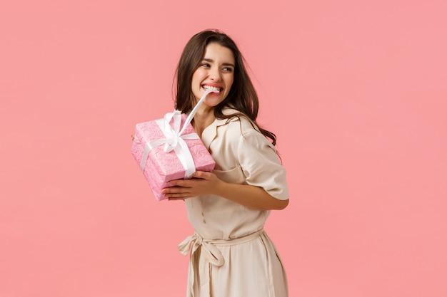 Glück, zärtlichkeit und feierkonzept. sorgloses fröhliches und fröhliches junges mädchen, das feiert, erstaunlichen geburtstag hat, beißenden knoten auf niedlichem geschenk, lächelt, verlockendes geschenk auspackt, rosa wand