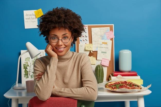 Glücklich angenehm aussehender student hat prüfungsvorbereitung zu hause, hält hand unter kinn, schaut mit lächeln direkt in die kamera, lässig gekleidet, genießt gemütliche atmosphäre im eigenen arbeitszimmer, coworking space