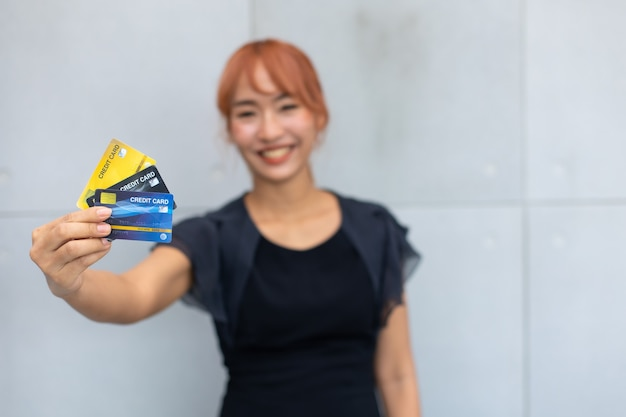 Glücklich aufgeregt erfolgreich schöne geschäftsfrau, die kreditkartenmodell auf der hand hält.