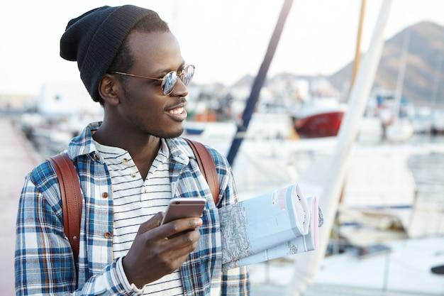 Glücklich aufgeregt sie afroamerikanischer männlicher rucksacktourist in stilvoller sonnenbrille und hut, der papierkarte unter seinem arm hält, mit online-navigations-app auf handy vor seiner reise