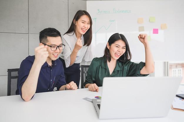 Glücklich aufgeregte junge asiatische geschäftsleute feierten erfolg oder leistung im besprechungsraum mit laptop