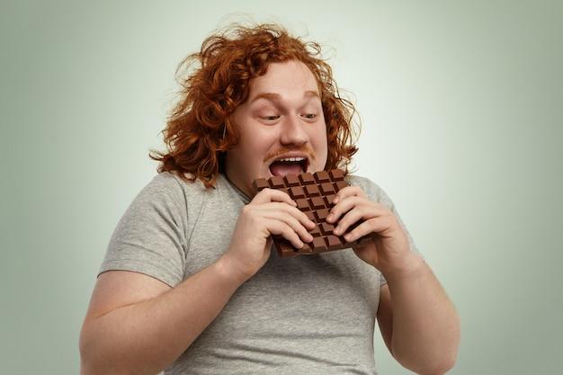 Glücklich aufgeregter junger molliger rothaariger mann, der den mund weit öffnet, während er eine tafel schokolade beißt und sich ungeduldig fühlt. lustiger kaukasischer mann im grauen t-shirt, das ungesundes, aber köstliches junk-food verbraucht