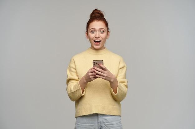 Glücklich aussehende frau mit ingwerhaar in einem brötchen gesammelt. tragen von pastellgelbem pullover und jeans. ein smartphone halten. überrascht von nachricht. isoliert über graue wand