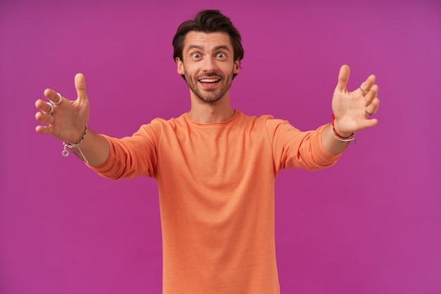 Glücklich aussehender kerl mit brünetten haaren und borsten. tragen eines orangefarbenen pullovers mit hochgekrempelten ärmeln. hat armbänder und ringe. will dich umarmen