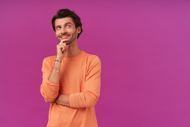 Glücklich aussehender, träumender kerl mit brünetten haaren und borsten. tragen eines orangefarbenen pullovers mit hochgekrempelten ärmeln. er berührte sein kinn