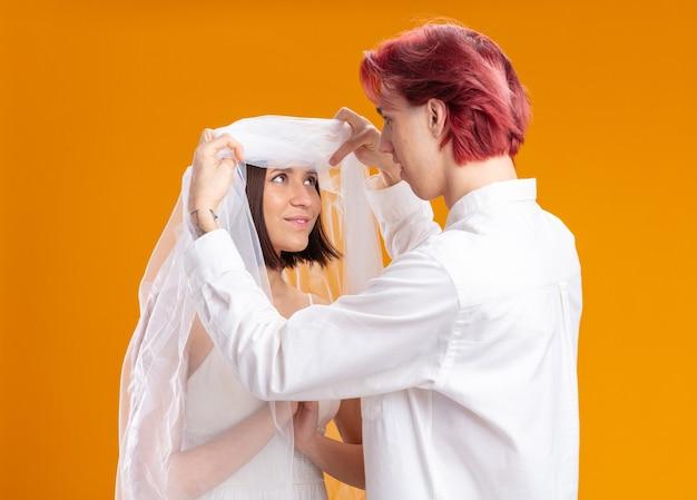 Glücklich aussehendes hochzeitspaar bräutigam und braut im hochzeitskleid unter schleier, bräutigam, der zuerst seine braut anschaut