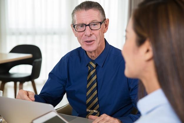 Glücklich business leader gespräch mit assistent in cafe