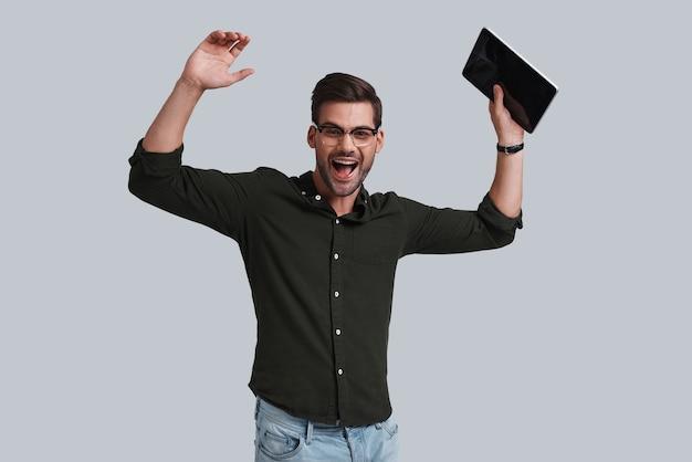 Glücklich, das projekt zu beenden! gut aussehender junger mann mit brille, der sein digitales tablet hält und gestikuliert, während er vor grauem hintergrund steht