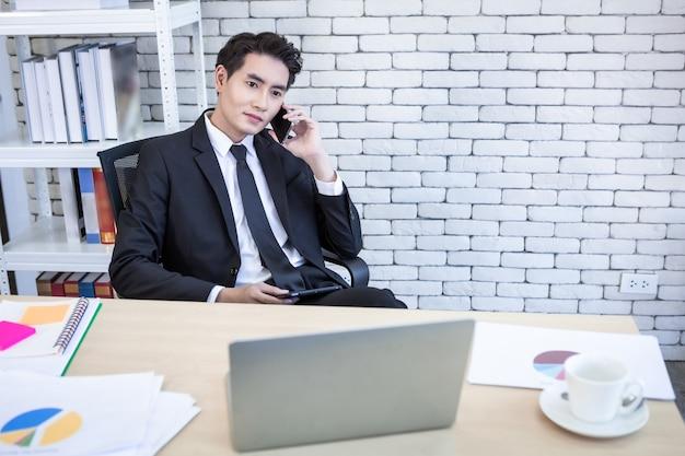 Glücklich der asiatische junge geschäftsmann hält smartphone-arbeiten mit und laptop-computer auf holztisch nach geschäftsverlusten im büroraumhintergrund ab.