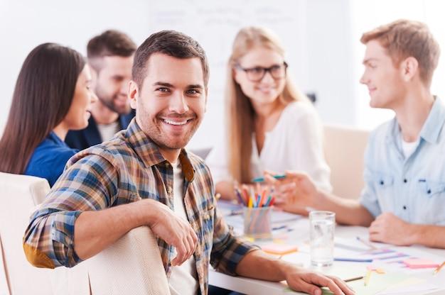 Glücklich, ein teil des kreativen teams zu sein. gruppe fröhlicher geschäftsleute in eleganter freizeitkleidung, die zusammen am tisch sitzen und etwas diskutieren, während ein gutaussehender mann in die kamera schaut und lächelt