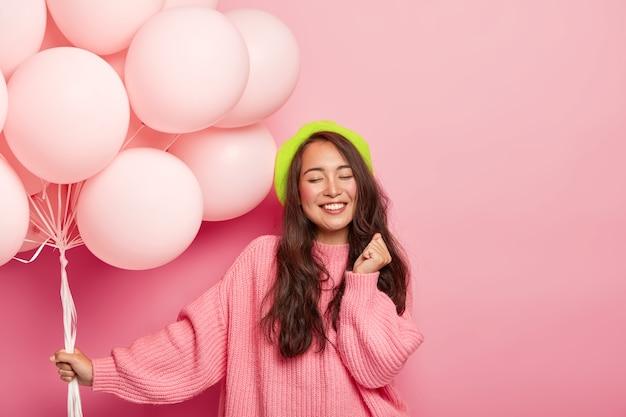 Glücklich erfreut brünette asiatische dame steht mit luftballons, genießt coole party mit freunden, trägt baskenmütze und losen pullover, feiert jubiläum