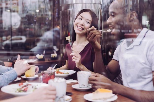 Glücklich erfreut zwei freunde, die sich im café entspannen, während sie sitzen und klatschen