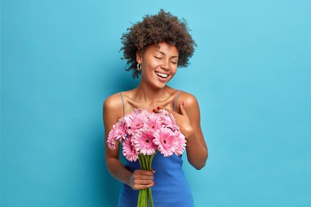 Glücklich erfreute frau genießt romantisches date bekommt strauß gerbera blumen von freund schließt augen vor vergnügen isoliert über blaue wand fühlt sich sehr dankbar