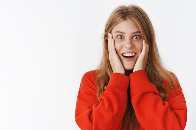 Glücklich erstaunte und überraschte frau kann nicht glauben, was sie mit offenem mund in erstaunen sieht und breit lächelt, die handflächen an die wangen drückt und erstaunt auf positive veränderungen nach der hautpflege reagiert