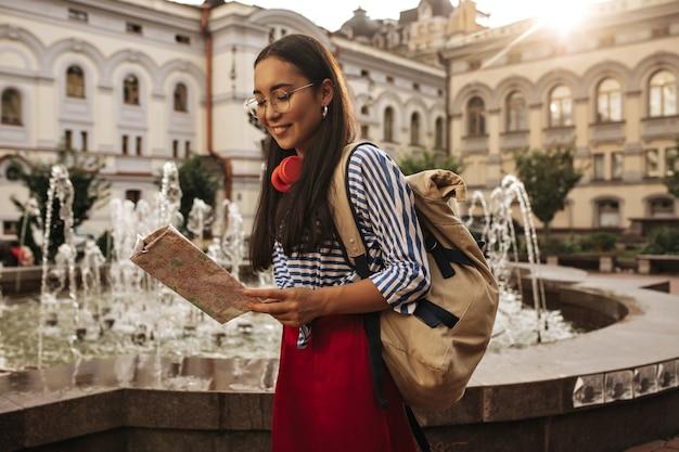 Glücklich gebräunte brünette asiatin in roter hose, gestreiftem hemd und brille lächelt, hält karte und rucksack in der nähe des brunnens