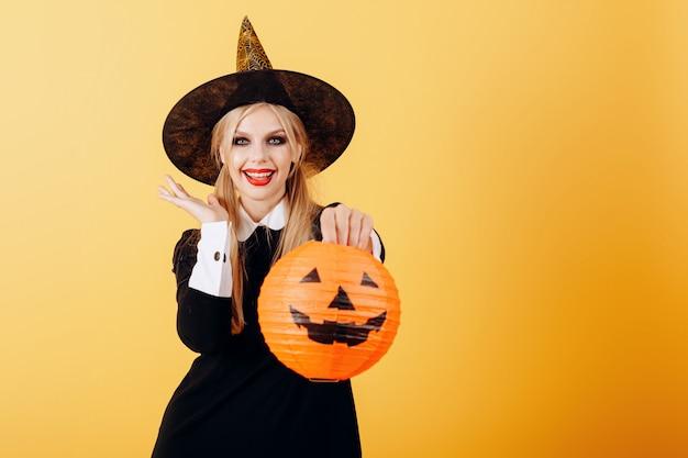 Glücklich gefühlfrau, die gegen einen gelben haltenen kürbis steht.