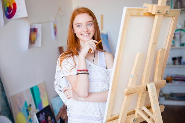 Glücklich inspirierte lächelnde künstlerin mit langen roten haaren, die mit bleistift zeichnen