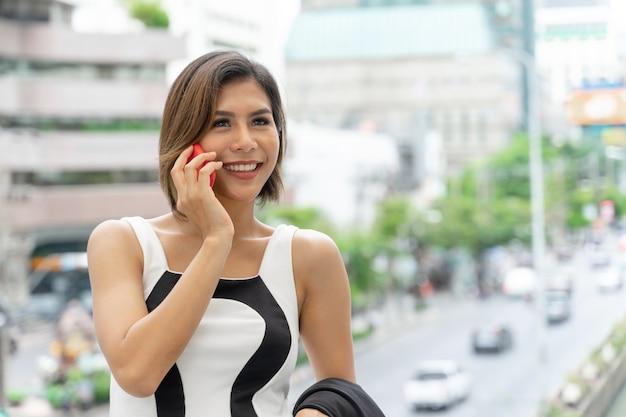 Glücklich junge hübsche frau, die mit smartphone, mit modernem gebäude spricht