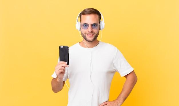 Glücklich lächelnd mit einer hand auf der hüfte und selbstbewusst, musik hören mit kopfhörern und einem smartphone