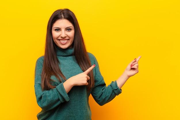 Glücklich lächelnd und mit beiden händen zur seite und nach oben zeigend, zeigt das objekt im kopierraum