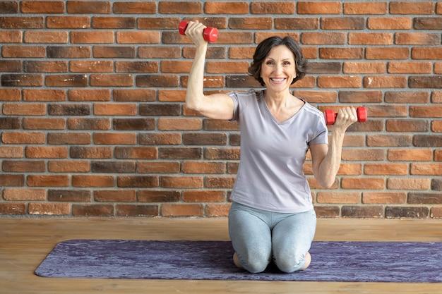 Glücklich lächelnde ältere frau fitnesspraktikerin, die zu hause auf fitnessmatte mit hanteln sitzt