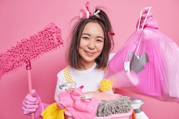 Glücklich lächelnde asiatische haushälterin hält plastiktüte und mopp, die mit den ergebnissen der hausarbeit zufrieden sind, räumt einzeln auf rosafarbenem hintergrund auf. waschen wasch- und hauswirtschaftskonzept