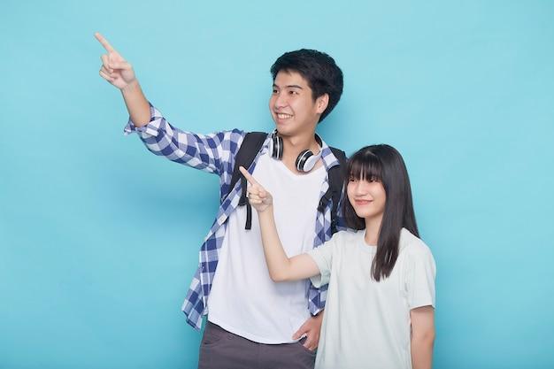 Glücklich lächelnde aufgeregte asiatische paartouristen, die hand auf leeren raum auf isolierter hellblauer oberfläche zeigen
