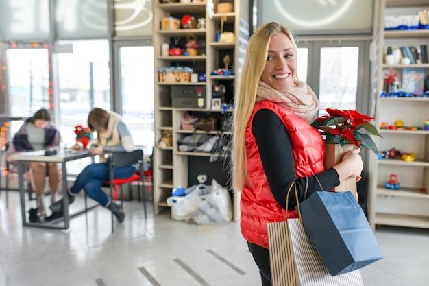 Glücklich lächelnde blondine im coffeeshop mit einkaufstüten