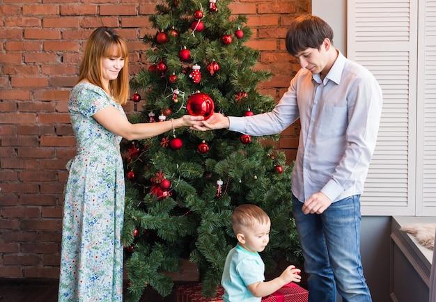 Glücklich lächelnde eltern und kind zu hause, die weihnachten feiern