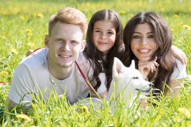 Glücklich lächelnde familie von eltern und tochter mit hund im park