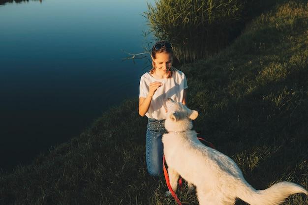 Glücklich lächelnde frau, die auf grasbewachsenem seeufer steht und niedlichen großen weißen hund auf roter leine nahe betrachtet