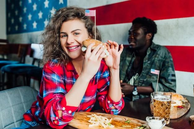 Glücklich lächelnde frau, die sich in der bar mit einem mann im café ausruht, redet, lacht, isst fast food.