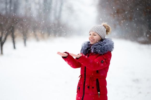 Glücklich lächelnde frau in roten winterjacke fang den schnee mit ihren handflächen, im freien, im park