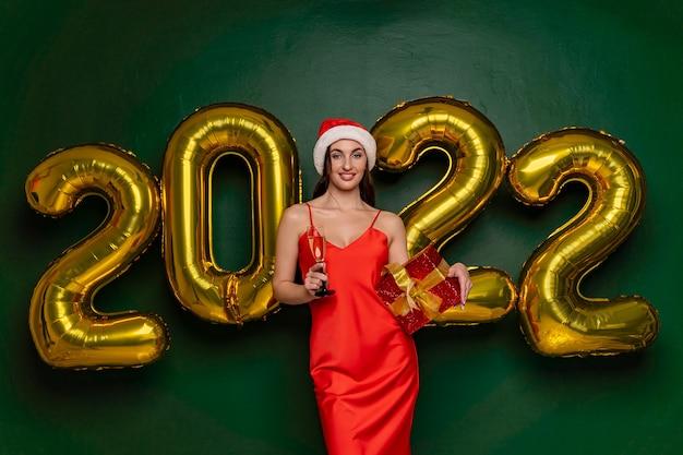 Glücklich lächelnde frau in weihnachtsmütze und rotem kleid hält ein glas champagner, das feiertag mit gold feiert...