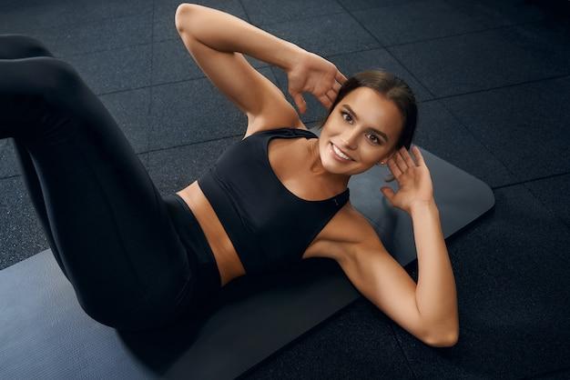 Glücklich lächelnde frau trainiert bauchmuskeln im fitnessstudio