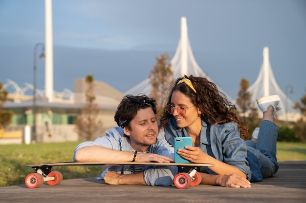 Glücklich lächelnde frau zeigt mann nachricht auf dem smartphone auf skateboard im freien im sommer stadtpark liegend