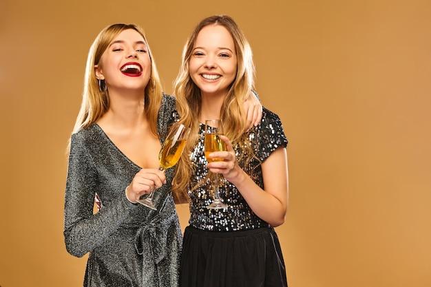 Glücklich lächelnde frauen in stilvollen glamourösen kleidern mit champagnergläsern auf goldener wand