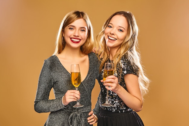 Glücklich lächelnde frauen in stilvollen glamourösen kleidern mit champagnergläsern