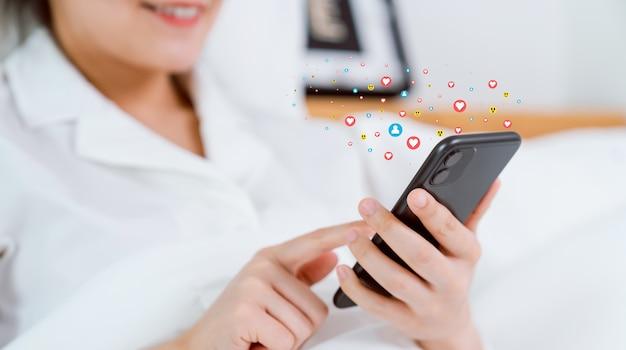 Glücklich lächelnde frauenhand mit smartphone lächeln und herz-symbol social media zeigen. konzept soziales netzwerk.