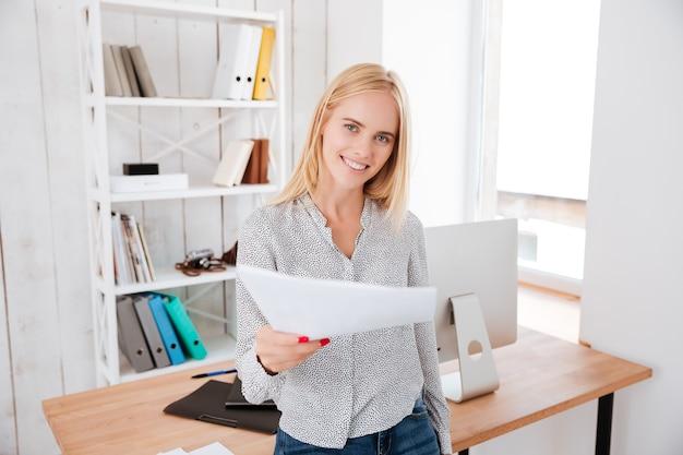 Glücklich lächelnde geschäftsfrau, die auf dem schreibtisch sitzt und dokument nach vorne gibt