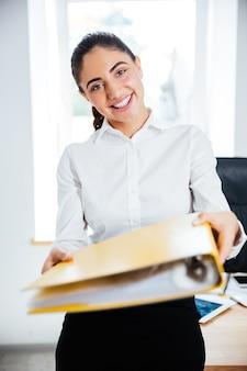 Glücklich lächelnde geschäftsfrau, die gelben ordner gibt und nach vorne im büro schaut