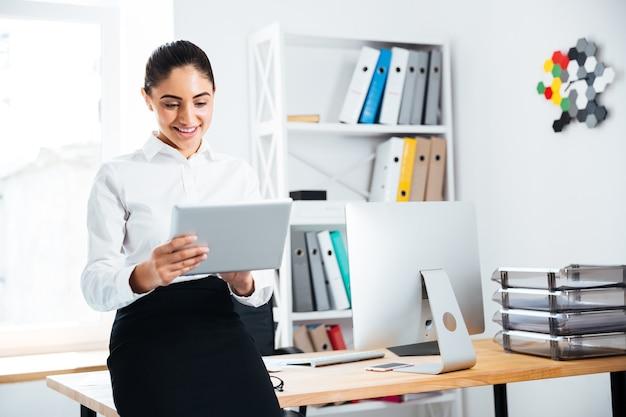 Glücklich lächelnde geschäftsfrau, die sich auf den schreibtisch stützt und pc-tablet verwendet
