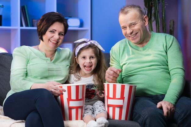 Glücklich lächelnde großmutter, großvater und kleine enkelin. unterhaltungsfernsehtechnologie. glückliche familie sitzt auf dem sofa und entspannt sich, indem sie wählt und fernsieht.