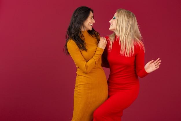 Glücklich lächelnde hübsche stilvolle frauen im gelben und roten herbstwintermode-strickkleid, das lokal auf roter wand aufwirft
