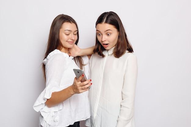 Glücklich lächelnde junge frau, die ihrer freundin fotos auf dem handy zeigt