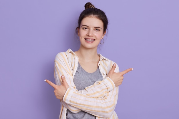 Glücklich lächelnde junge frau, die weißes hemd trägt, haarknoten hat, mit zeigefingern auf beide seiten zeigt, frau, die gegen lila wand steht, schaut in die kamera, drückt positiv aus.