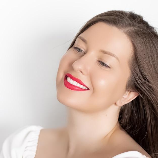 Glücklich lächelnde junge frau mit perfekten weißen zähnen und schönem, gesundem lächeln saubere haut und natürliches make-up weibliches gesichtsporträt mit positiver emotion, schönheit, wellness und hautpflege-anzeige
