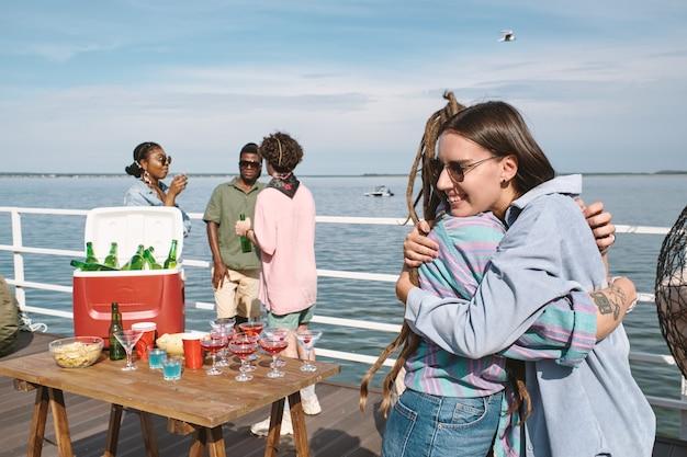 Glücklich lächelnde junge frau mit sonnenbrille, die ihre freunde umarmt, die sie auf der geburtstagsfeier am pier getroffen hat?